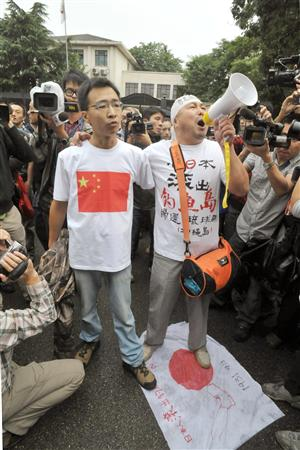 北京の日本大使館前で日の丸を踏みつけ、抗議する男性=18日午前2010年9月