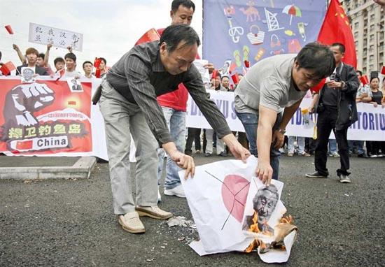 【反日】ルーマニアで「天皇の写真」と「日の丸」を燃やす反日中国人の写真2012年9月