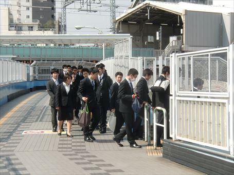 南千住駅前歩道橋を渡る就活生たち