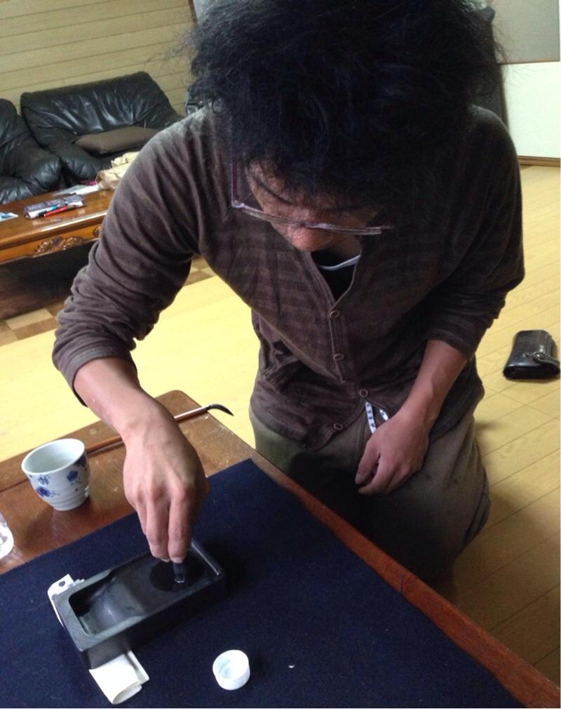 洞爺堂の堂主「やすじ」さんにも墨を磨ってもらう。撮影:遠藤夕幻