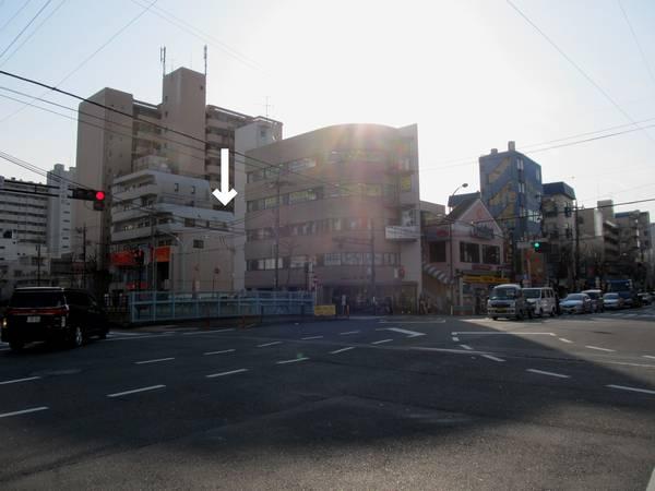地上にある方南町交差点。新しい駅ビルは左奥の白い矢印を付けた空地に建設される。