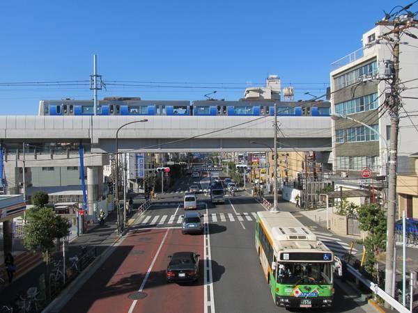 明治通りの踏切南側にある歩道橋から踏切と高架橋を見る。
