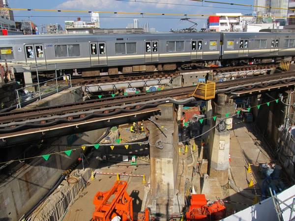 南側にある歩道橋から京王井の頭線の橋梁とその下で行われている杭の打ち込み作業を見る。
