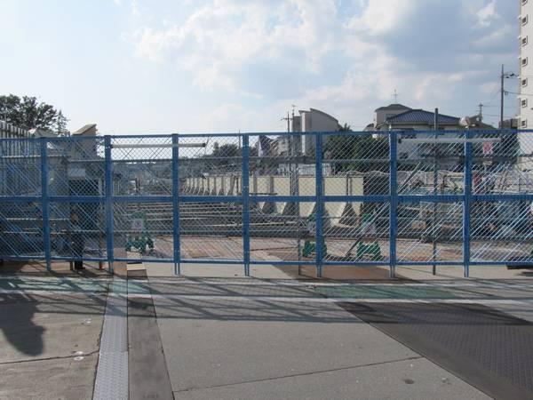 旧世田谷代田1号踏切から梅ヶ丘駅方向を見る。手前の橋桁は環状7号線の上に架かっていたもので2014年1月に撤去された。フェンスの向こうに地上に出てきた線路が見える。