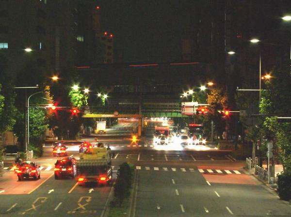 靖国通りの淡路町交差点付近の歩道橋から見た試運転列車通過中の様子。縦貫線の高高架橋の上をオレンジ色のLEDが点々と過ぎ去っていく。