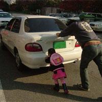 車を押す親子